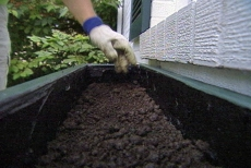 layering soil in the window box planter
