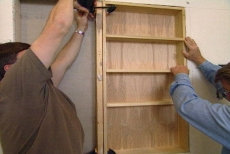 positioning the shelf unit between the studs