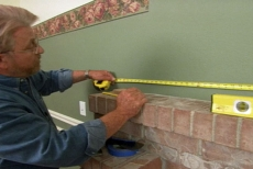 measuring for a decorative wall frame above the fireplace