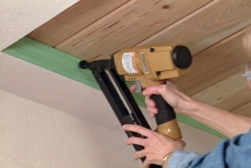 Using a nail gun to nail the trim into place.