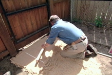 leveling sand with screed rails and a two-by-four