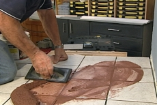 Spreading grout at a 45 degree angle with a grout float