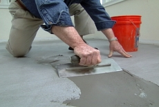 Using a trowel to apply a final layer of floor leveler