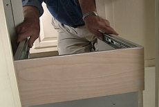 positioning the pull-out waste bin base against the cabinet