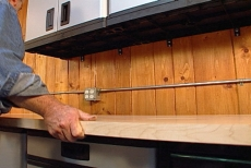 positioning the hardwood countertop in the garage workshop