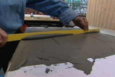 Using a straight edge to screed the excess mortar