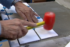 Tapping tiles into place with a plastic mallet