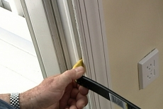 Using a pry bar to pull the interior trim away from the wall