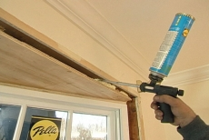 spraying foam sealant into the framing crevice