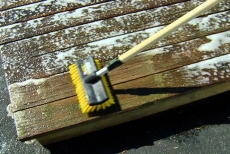 brushing the deck restoration cleaning solution