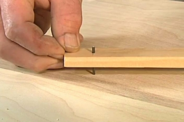 inserting the nail into the hole