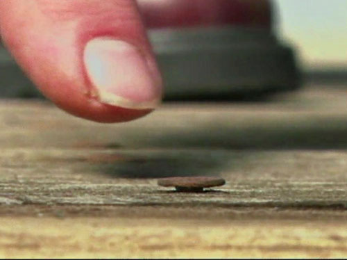 A protruding deck nail in a wooden deck